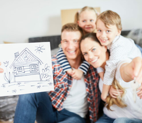 Glückliche Familie und Kinder zeigen Bild als Symbol für Eigenheim und Hauskauf
